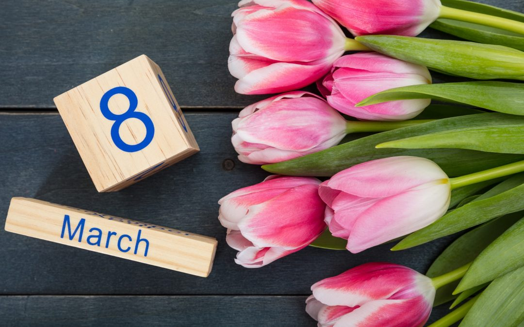 Women's day concept. Pink tulips and the March 8th date on blue background
